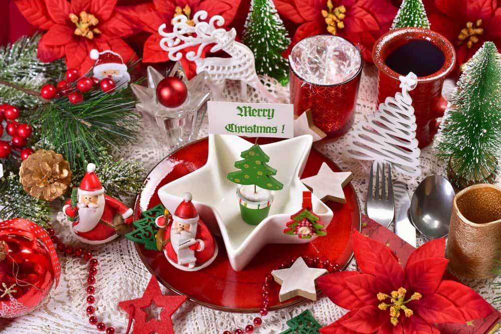 Las flores de navidad en la mesa le dan un toque fresco y natural. Mezcla con adornos como estrellas, pequeños Santas y velas para resaltar la decoración de la mesa.