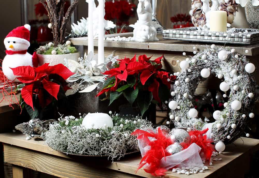 Elige una mesa para hacer un bello arreglo con adornos en tonos blanco y plata mezclados con las flores de navidad.