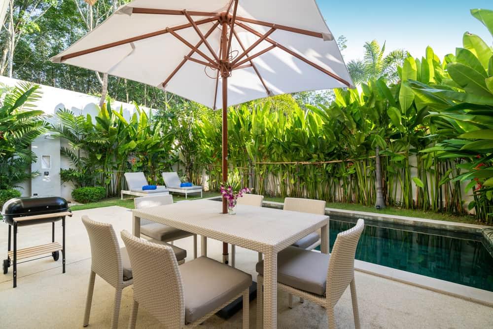En el diseño de jardines pequeños incluye una mesa con paraguas y comodas sillas para pasar largos ratos en tu jardín.